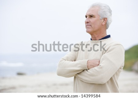Man at the beach with arms crossed - stock photo