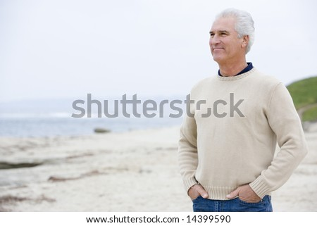 Man at the beach with hands in pockets - stock photo
