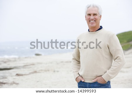 Man at the beach with hands in pockets smiling - stock photo