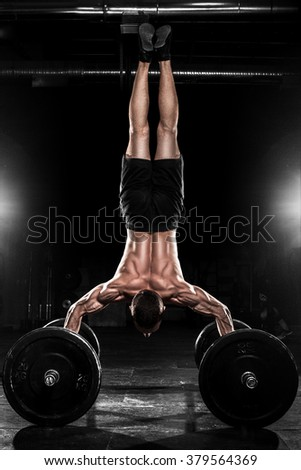 man at the gym CrossFit performs gymnastic elements - stock photo