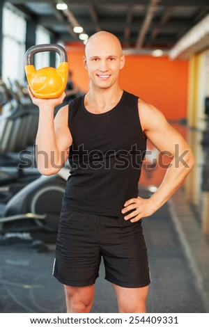 Man at the gym doing exercise with kettlebell