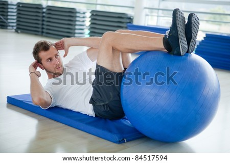 Man at the gym doing exercises for his abs with a Swiss ball - stock photo