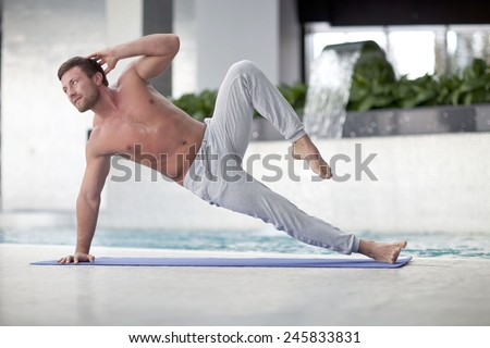 Man at the gym doing stretching exercises and smiling on the floor - stock photo