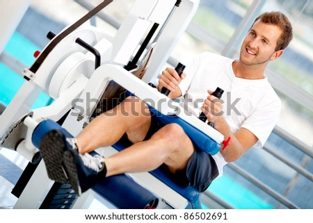 Man at the gym exercising on a machine - stock photo
