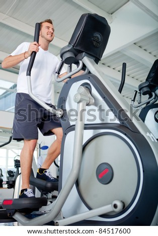 Man at the gym exercising on the xtrainer machine - stock photo