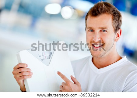 Man at the gym holding a scale - lose weight concepts - stock photo