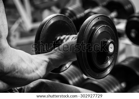 Man at the gym. Man makes exercises with barbell. Sport, power, dumbbells, tension, exercise - the concept of a healthy lifestyle. Article about fitness and sports. - stock photo