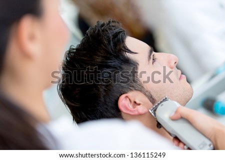 Man at the hairdresser getting a haircut - stock photo
