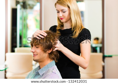 Man at the hairdresser, she is cutting his hair