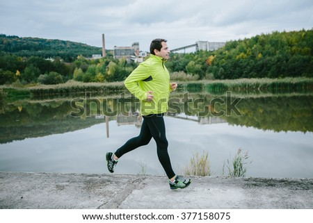 Man at the lake running on conrete path - stock photo