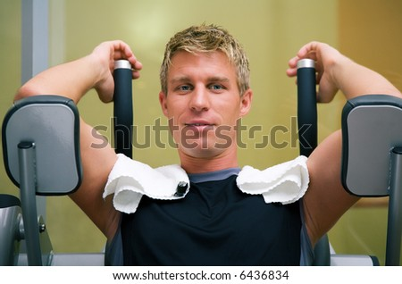 Man at the machine in a gym having a break - stock photo