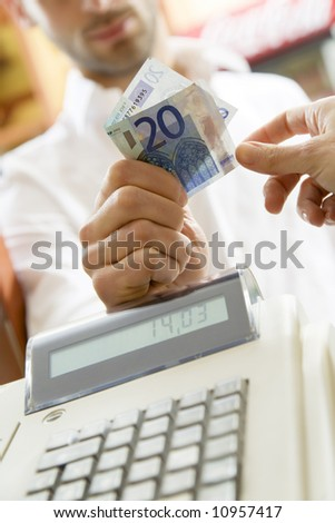 man at the supermarket giving 20 Euro to the cashier - stock photo