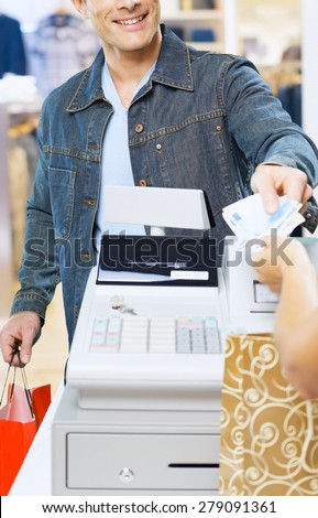 man at the supermarket giving  Euro to the cashier - stock photo