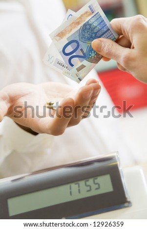 man at the supermarket paying 20 Euro to the cashier - stock photo