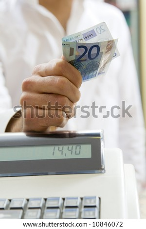 man at the supermarket standing near the cash box and holding 20 Euro