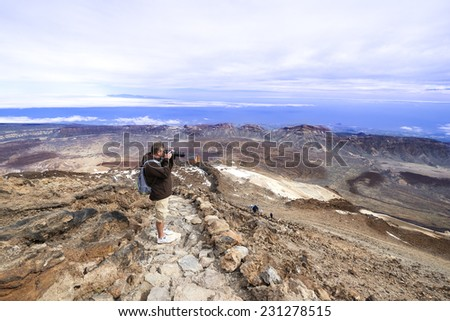Man at  top of volcano Teide with blue sky. Teide is the highest volcano in Europe (Teide National Park, Tenerife, Canary islands, Spain).