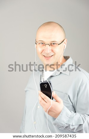 man at 38 use smart phone, bold head grey shirt against grey background  - stock photo