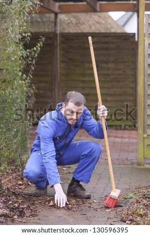 man at work.   groundskeeper (caretaker service) cleaning a garden path.