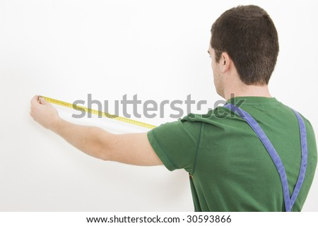 Man at work measure the wall with tape measure - stock photo