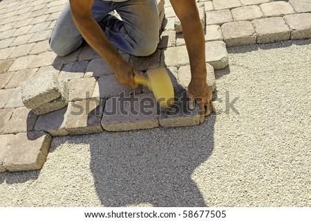 man at work paving stones with rectangular - stock photo