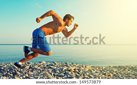 man athlete running by the sea at sunset outdoors - stock photo