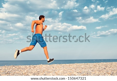 man athlete runs by the sea at sunset outdoors - stock photo