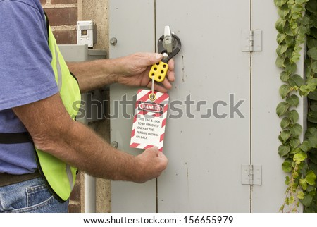 man attaching a lockout tag to an electrical control panel - stock photo