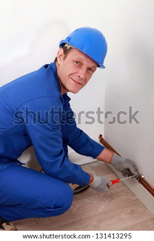 Man attaching copper pipe to wall - stock photo