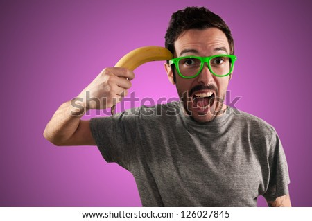 man attempting suicide with a banana on pink background