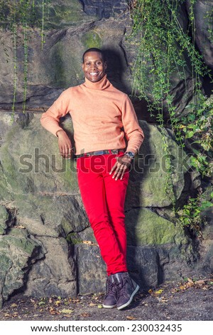 Man Autumn Casual Fashion. Dressing in light orange sweater with high collar, red pants, patterned boot shoes, wearing wristwatch, a young black guy is standing against rocks, smiling, relaxing. - stock photo