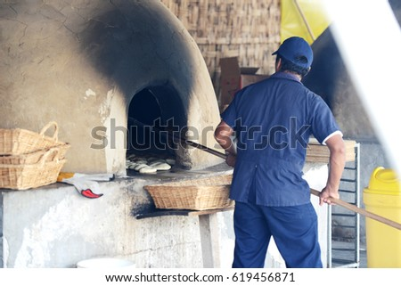 Man baking bread ina a rustic traditional oven in Peru