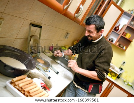 man baking Roll wafers - stock photo