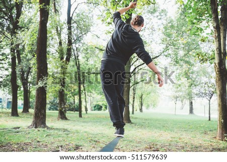 Man balancing a tightrope or slackline outdoor in a city park in autumn - slacklining, balance, training concept