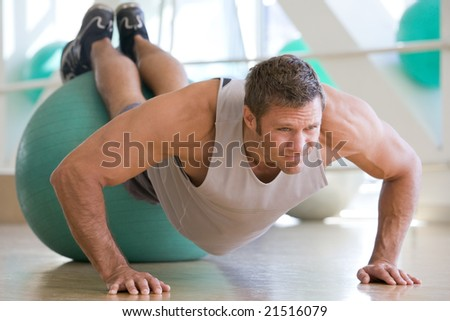 Man Balancing On Swiss Ball At Gym