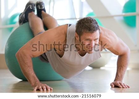 Man Balancing On Swiss Ball At Gym - stock photo
