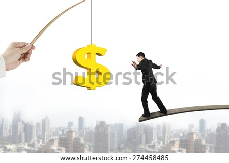 Man balancing on wood board for 3D golden dollar sign bait from fishing rod hand holding, with urban scene background - stock photo