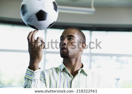 Man balancing soccer ball on finger - stock photo