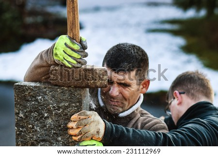 man bash steles by ramming with hammer - stock photo