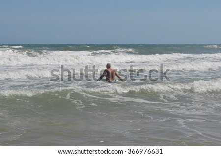 Man bathing in the sea when a big wave