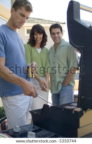 Man BBQ's while couple watches - stock photo