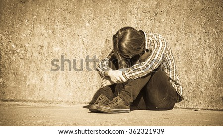 Man bearded long hair sitting alone by grunge wall outdoor, covering his head in shoulders. Unemployment depression or sadness concept. - stock photo