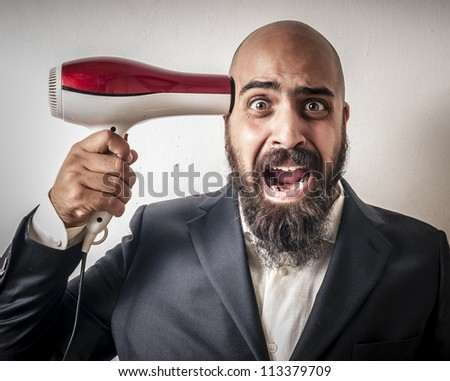 man bearded with a suit and hairdryer on white background - stock photo