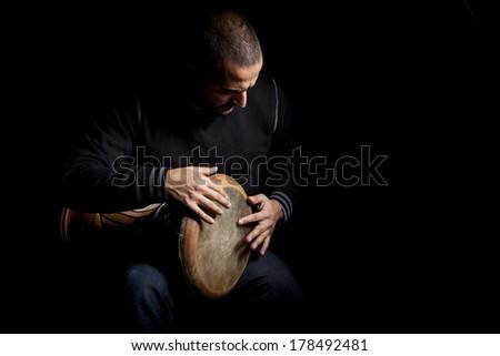 man beating tomtom on black - stock photo
