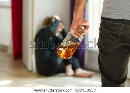 Man beating up his wife illustrating domestic violence - stock photo