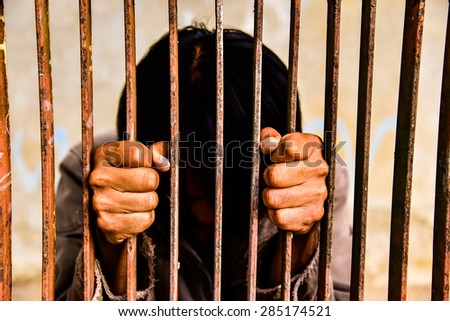 Man behind jail bars reaching out - stock photo