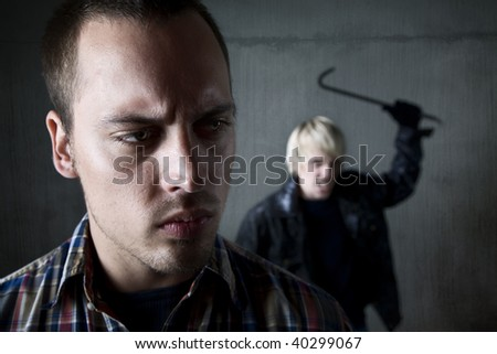 Man being assaulted by criminal with crowbar - stock photo