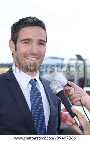 Man being interviewed by the media - stock photo