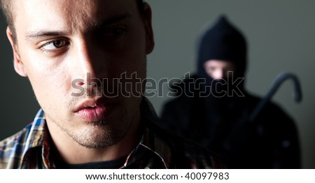 Man being stalked by criminal with crowbar - stock photo