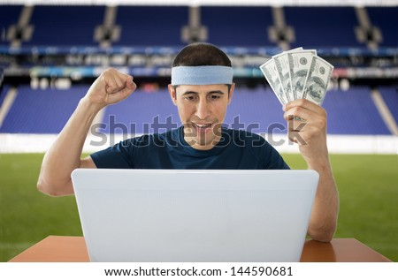 man betting online and making a lot of dollar in stadium - stock photo