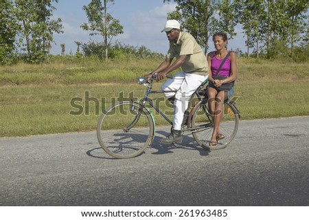 Man bicycling with woman on the back of the bike through the countryside of central Cuba